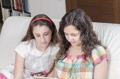Muchacha y mujer que se sientan en un sofá que mira su tableta Foto de archivo libre de regalías