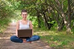 Muchacha y ordenador portátil al aire libre Foto de archivo