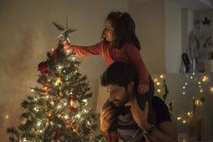 Muchacha y papá que ponen el árbol de navidad con la estrella, luces y Imagenes de archivo