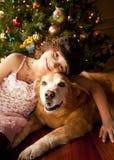 Muchacha y perro con el árbol de navidad Foto de archivo libre de regalías