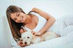 Muchacha y perro en cama Imagen de archivo