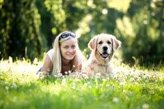 Muchacha y perro en hierba Fotografía de archivo libre de regalías