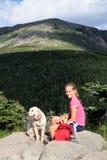 Muchacha y perro en montañas Imagenes de archivo