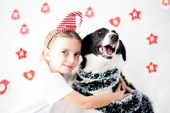 Muchacha y perro felices en la Navidad Foto de archivo