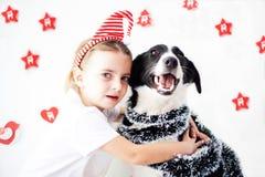 Muchacha y perro felices en la Navidad Imagen de archivo