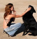 Muchacha y perro negro Foto de archivo libre de regalías