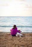 Muchacha y perro por el océano Imagenes de archivo
