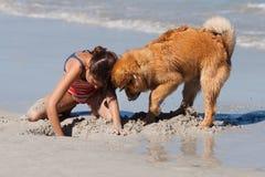 Muchacha y perro que cavan junto un agujero en la arena Imagen de archivo