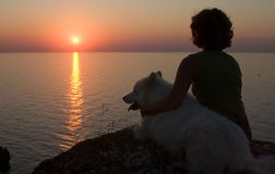 Muchacha y perro que miran a la puesta del sol sobre un mar Foto de archivo