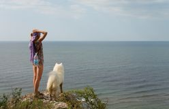 Muchacha y perro que se colocan en precipicio Foto de archivo libre de regalías