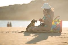 Muchacha y perro que se divierten en la playa Perro descuidado lindo de la estancia adoptado cuidando a la mujer Gafas de sol que Fotos de archivo libres de regalías