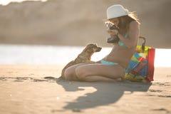 Muchacha y perro que se divierten en la playa Perro perdido descuidado lindo adoptado cuidando a la mujer Gafas de sol que desgas Imágenes de archivo libres de regalías