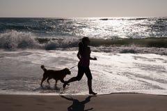Muchacha y perro que se ejecutan en la playa Imagen de archivo libre de regalías