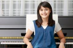 Muchacha y piano asiáticos Imagenes de archivo