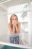 Muchacha y refrigerador vacío Imagenes de archivo