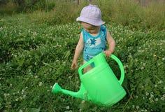 Muchacha y regar-crisol de Litlle Foto de archivo libre de regalías