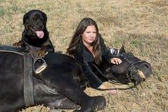 Muchacha y rottweiler jovenes del montar a caballo Imagen de archivo
