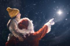 Muchacha y Santa Claus que miran la estrella de la Navidad Imagen de archivo libre de regalías