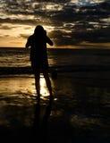 Muchacha y su cámara durante la puesta del sol Imagen de archivo libre de regalías