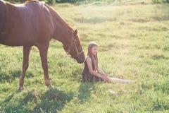 Muchacha y su caballo en el campo iluminado por el sol Imagenes de archivo