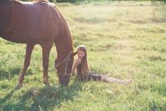 Muchacha y su caballo en el campo iluminado por el sol Imágenes de archivo libres de regalías