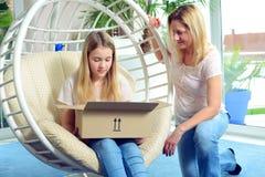 Muchacha y su madre que abren un paquete junto Imagen de archivo