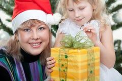 Muchacha y su madre que abren un regalo de la Navidad Fotos de archivo