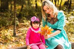 Muchacha y su madre que juegan al aire libre con las hojas de arce otoñales Bebé que escoge las hojas de oro imagenes de archivo