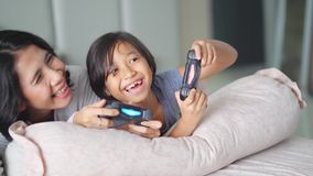 Muchacha y su madre que juegan la videoconsola metrajes