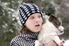 Muchacha y su perrito afuera en nieve Imagen de archivo