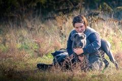 Muchacha y su perro gris Foto de archivo