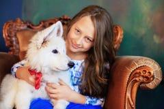 Muchacha y su perro que se sientan en una silla El concepto de la amistad a Imagenes de archivo