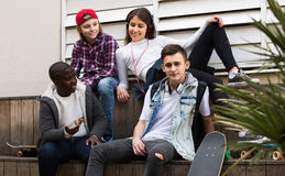 Muchacha y tres muchachos que cuelgan hacia fuera al aire libre y que discuten el somethin Fotografía de archivo