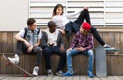 Muchacha y tres muchachos que cuelgan hacia fuera al aire libre y que discuten el somethin Fotos de archivo