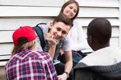 Muchacha y tres muchachos que cuelgan hacia fuera al aire libre y que discuten el somethin Foto de archivo libre de regalías