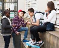 Muchacha y tres muchachos que cuelgan hacia fuera al aire libre y que discuten el somethin Fotos de archivo libres de regalías