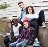 Muchacha y tres muchachos que cuelgan hacia fuera al aire libre y que discuten el somethin Fotografía de archivo libre de regalías