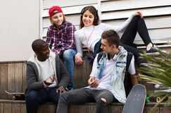 Muchacha y tres muchachos que cuelgan hacia fuera al aire libre y que discuten el somethin Imagenes de archivo
