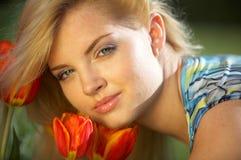Muchacha y tulipanes hermosos Imágenes de archivo libres de regalías