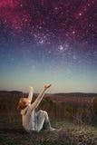 Muchacha y un cielo estrellado. Fotografía de archivo