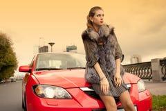 Muchacha y un coche rojo imagenes de archivo