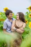 Muchacha y un hombre joven en el campo de girasoles Fotos de archivo libres de regalías