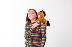 Muchacha y un juguete del caballo Imagenes de archivo