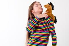 Muchacha y un juguete del caballo Fotografía de archivo libre de regalías