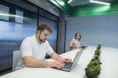 Muchacha y un trabajo del hombre joven sobre los ordenadores portátiles en el mismo taller Trabajo en coworking La situación en l foto de archivo