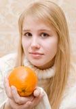 Muchacha y una naranja Imagenes de archivo