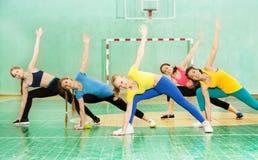 Muchachas activas que practican la gimnasia en pasillo de deportes Foto de archivo libre de regalías