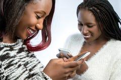 Muchachas adolescentes africanas que mecanografían en los teléfonos elegantes Imagen de archivo