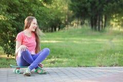 Muchachas adolescentes con con el monopatín en parque del verano Fotos de archivo