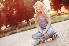 Muchachas adolescentes con con el monopatín en parque del verano Imágenes de archivo libres de regalías